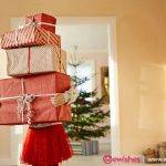 Little girl holding tall stack of christmas presents, standing in living room